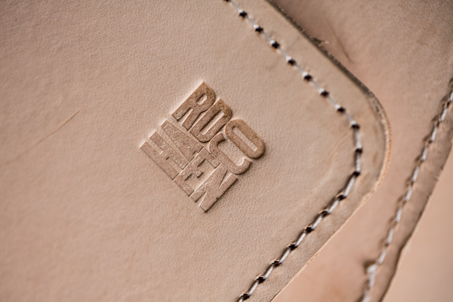Leather detail image of stitching and embossed logo